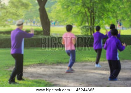 Blur image People practising tai chi in the park