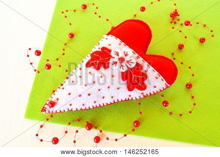 Handmade felt heart. Symbol of Valentines Day, felt white and red heart toy on green background