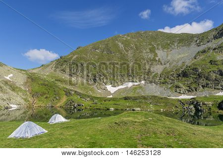 Mountain landscape with camping tents near the lake.