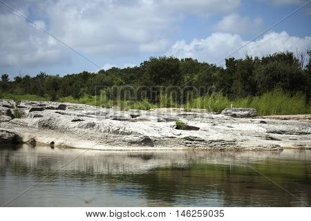 Arid terrain set against shallow pool, green trees and blue sky.