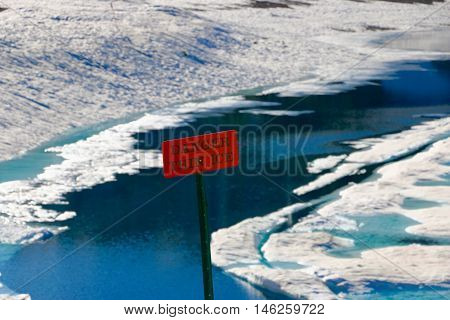 A danger thin ice sign placed next to a frozen lake
