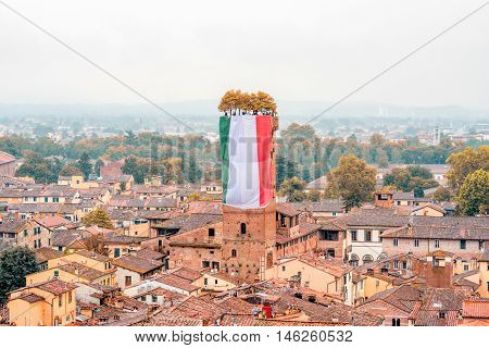 Aerial cityscape view on the old town of Lucca with Guinigi tower from the clock tower at the foggy weather in Italy