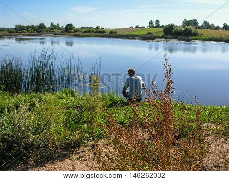 Fisherman with a fishing rod in anticipation of biting at the lake