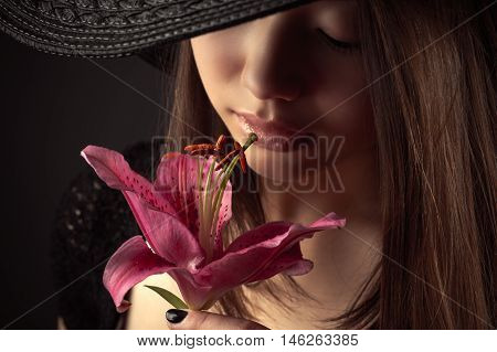 Korean teenager girl with lily flower isolated on black background