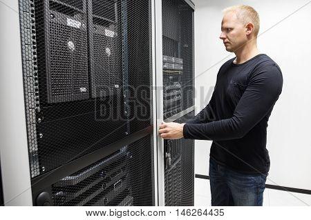 Mid adult male computer engineer opening server rack door in large data center