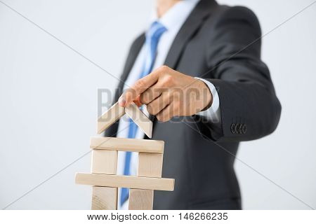 Close up of businessman building tower of wooden blocks