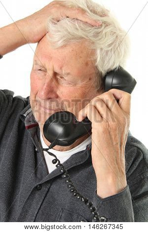 Senior gentleman age 78 hearing bad news on a vintage phone.