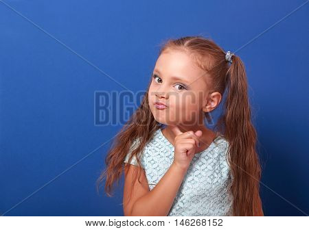 Serious Makeup Thinking Kid Girl With Long Hair Looking On Blue Background With Empty Copy Space