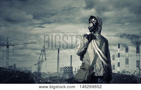 Man survivor in gas mask on industrial gray background