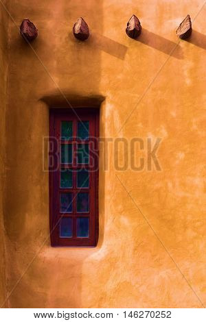 Southwestern adobe style building with a small window taken in Santa Fe, NM