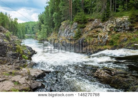 Wild waterfall in Northern Europe. Landscape with forest mountains and the powerful flow of the waterfall of the North. Beautiful view of the nature of wild places.