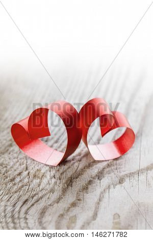 Two red small ribbon hearts on wooden background