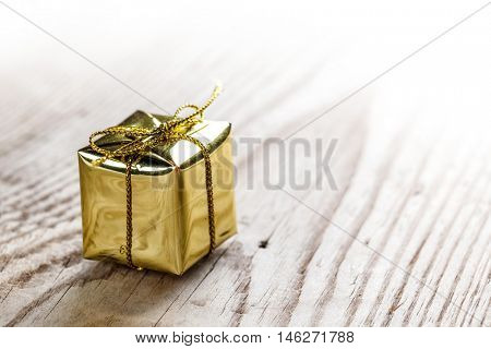 One small golden gift box on wooden background macro
