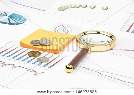 Business still-life of a diagram, magnifier, coins, sticker