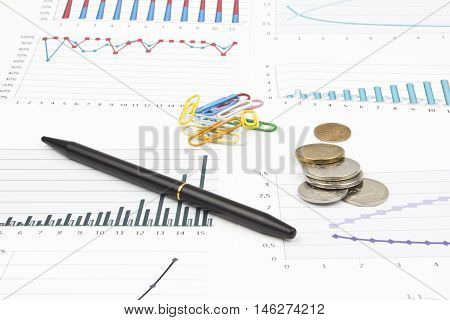 Business still-life of a pen, diagram, coins, paperclip