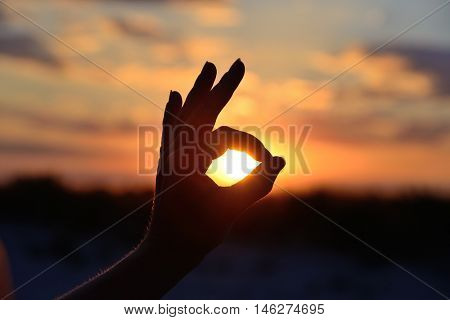 okay gesture on the background of the sun