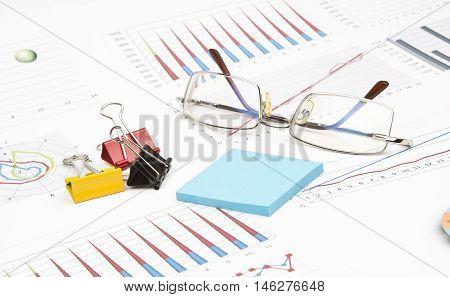 Business still-life of sticker, graphs, eyeglasses, paperclip
