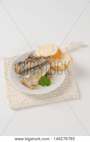 sardines with slices of bread on white plate