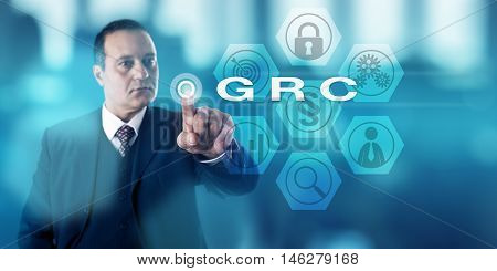 Experienced corporate governance officer is activating GRC onscreen. Business concept and information security metaphor for Governance Risk Management and Compliance procedures and processes.