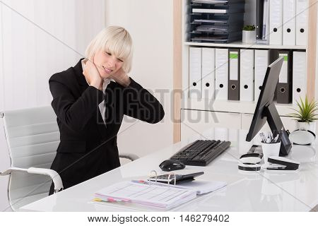 Young Businesswoman Suffering From Neckache At Desk In Office
