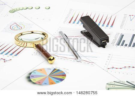 Business still-life of a charts, graphs, pen, magnifier, stapler