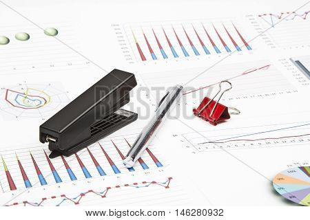 Business still-life of a charts, graphs, paperclips, stapler