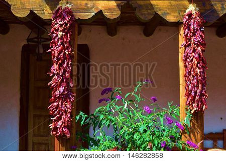 Hanging red chili peppers at a southwestern adobe style building which is a New Mexico custom taken in Santa Fe, NM