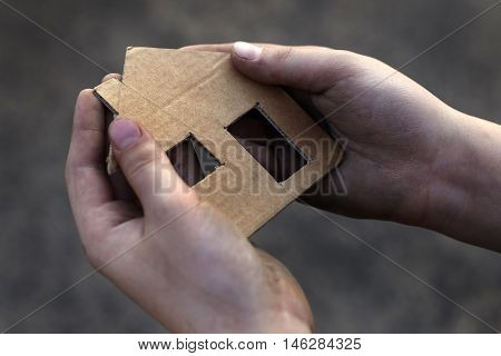 homeless boy holding a cardboard house dirty hand