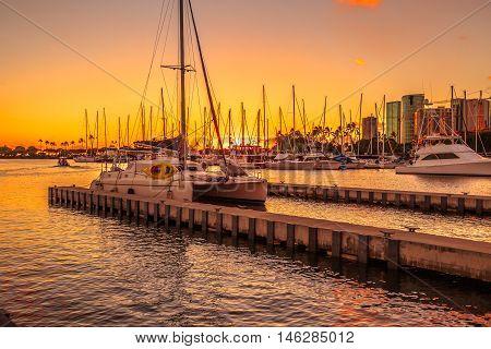 Catamaran docked at the Ala Wai Harbor at sunset. Ala Wai Yacht Harbor is the largest yacht harbor of Hawaii, situated between Waikiki and downtown Honolulu.