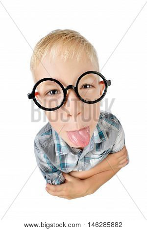 Wide angle close-up funny portrait of boy a student in shirt in glasses looking at camera showing tongue isolated on white background. School preschool