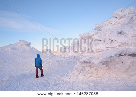 Tourist walking in snowshoes in the mountains. Winter landscape with snow and firn