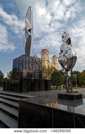 RESITA ROMANIA - SEPTEMBER 1 2016: New monument and Orthodox church in Resita Romania.