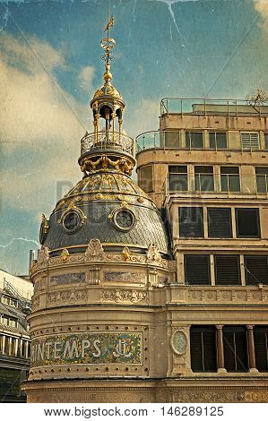 Old postcard with part of facade from store Printemps (founded in 1865) in Paris - largest beauty Department Store in world with 45000 square meters of shopping. Vintage processing.