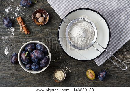 Plum pie cooking process. Powdered sugar, plum fruits and spices on dark wooden background.
