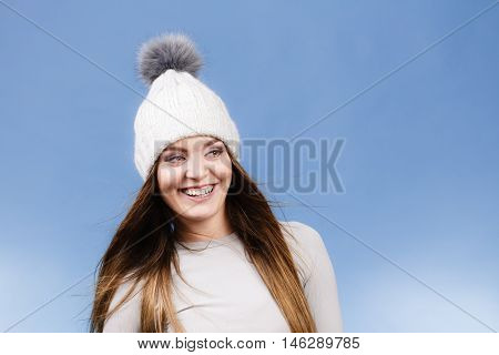 Attractive woman in winter cap and gray sports thermolinen underwear for skiing training studio shot on blue. Long sleeves top