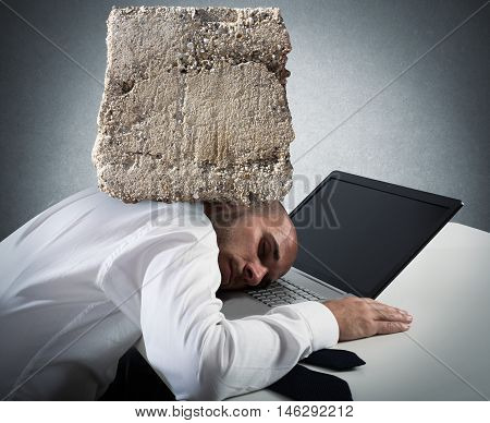 Businessman sleeping on a computer keyboard with a big rock over his head
