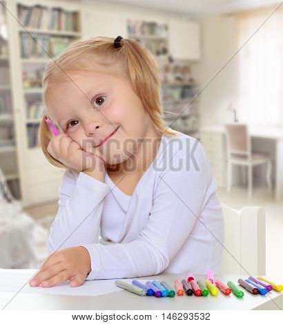 The concept of family happiness, and preschool education of the child , against a child's room with bookshelves.Pretty little blonde girl drawing with markers at the table.Girl put head on his hand