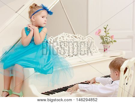 Funny kids posing near the old white Grand piano. The boy presses the button , and the girl helps him.