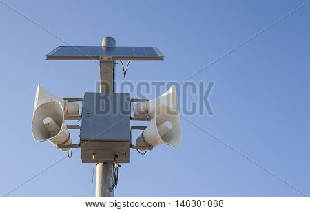 Solar-powered megaphones pole against blue sky background
