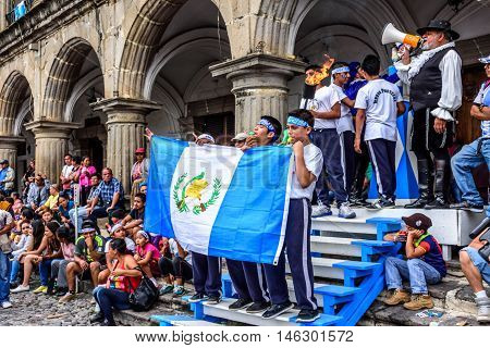 Antigua Guatemala - September 14 2015: Locals pose for photos with Guatemalan flag & lit torch outside city hall during Guatemalan Independence Day celebrations