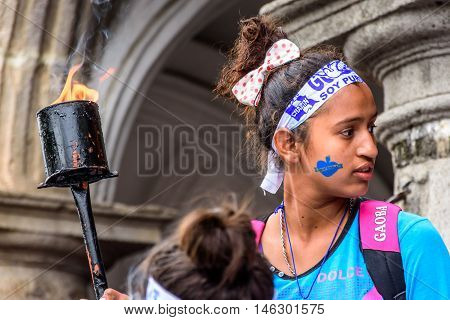 Antigua Guatemala - September 14 2015: Patriotic girl with torch & Guatemala headband & face stamp during Guatemalan Independence Day celebrations