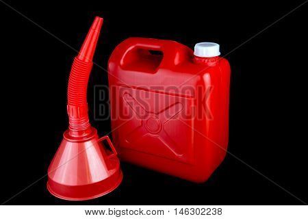 Red fuel container and funnel isolated on a black background