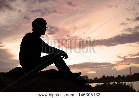 man sitting on rock watching the sunset