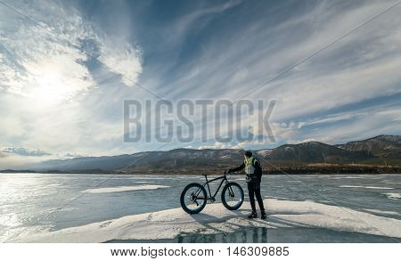 Fatbike (also called fat bike or fat-tire bike) - Cycling on large wheels. Cyclist holding a bike and watching the sunset. They are standing on the frozen lake.