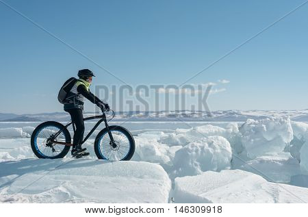 Fatbike (also called fat bike or fat-tire bike) - Cycling on large wheels. A cyclist sits on the bike on the ice.