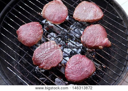 fresh raw red beef fillet on black bbq grill over hot charcoal