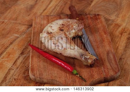 grilled chicken thighs on wooden cut board and red hot chili pepper and stainless steel knife over light wooden table