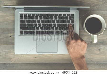 hand press enter key button on laptop with coffee cup on wooden background and vintage filter