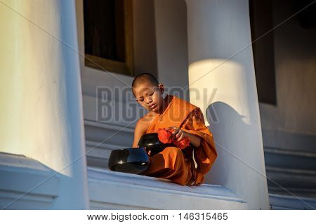 Young Novice monks sit cleaning alms bowl in monastery the big window temple at Ayutthaya historical park in Thailand
