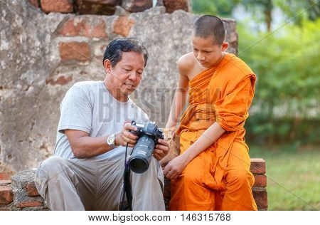 Old man photographer and young novice looking for photo camera in old temple at Ayutthaya Province Thailand